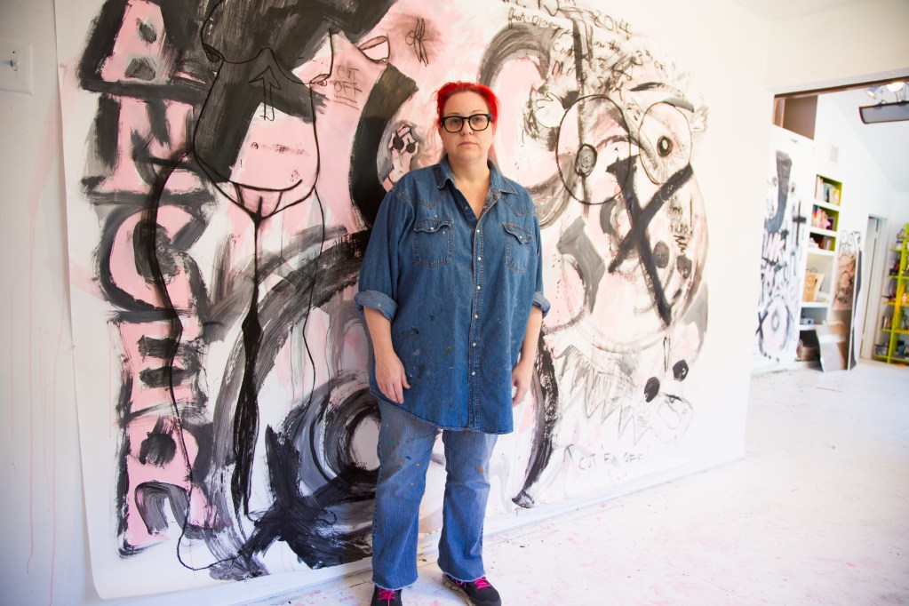 "Jan Johnson / Thedra in front of a piece called ""Fuck Cancer"" which is about 10' x 10' acrylic on paper."